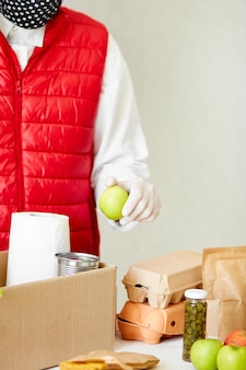 Волонтер в защитной медицинской маске и перчатках кладет еду в ящик для пожертвований
