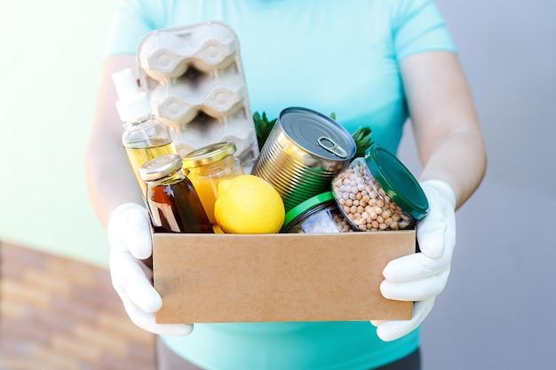 Волонтер в белых перчатках держит картонную коробку с основными продуктами питания