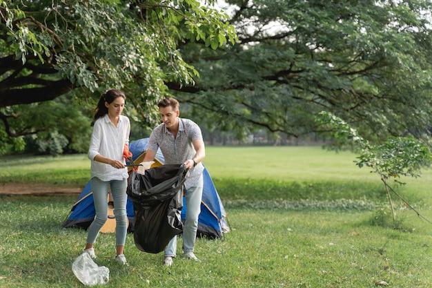 환경을 깨끗하게 유지하기 위해 공원에서 쓰레기를 줍기 위해 걸어가는 장갑을 끼고 자원 봉사 연인 부부