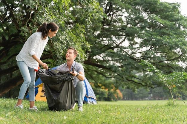 公園でゴミ拾いをするために歩いている手袋をはめたボランティア愛好家のカップル環境をきれいに保つために