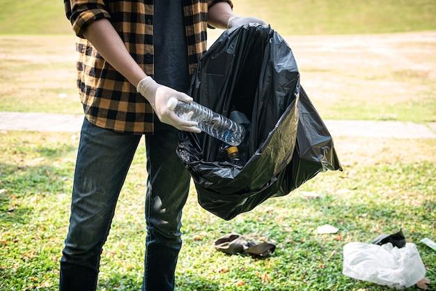 Мужчина-волонтер в перчатках собирает пластиковую бутылку в черный пластиковый пакет для уборки парка во время экологической деятельности для сбора мусора