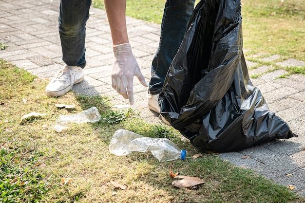 Человек-волонтер в перчатках идет и останавливается, чтобы собрать пластиковые бутылки в черный пластиковый пакет для уборки парка во время экологической деятельности для сбора мусора