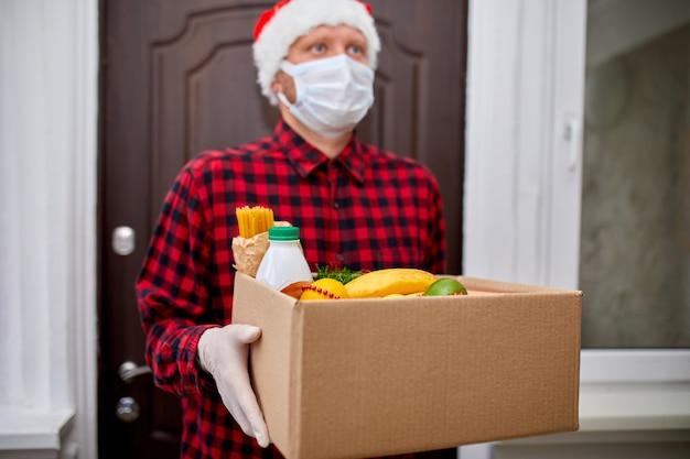 Мужчина-волонтер в шляпе санта-клауса и защитной маске и перчатках с доставкой коробки для пожертвований на дом в рождественские праздники курьер с упаковочной коробкой с бесконтактной доставкой еды служба карантина коронавируса