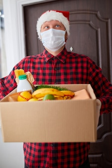 Volunteer man in santa hat and protective mask and gloves delivery donation box at home in christmas holiday courier with packing box with food contactless delivery service quarantine  coronavirus
