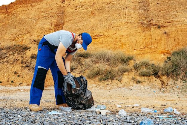 海の近くで集められたゴミの完全な袋を持ってビーチに立っているボランティアの男