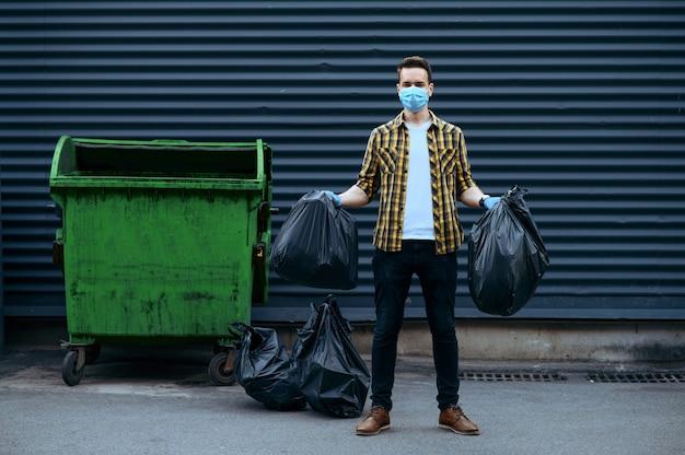 Volunteer in mask holds plastic trash bags outdoors, volunteering