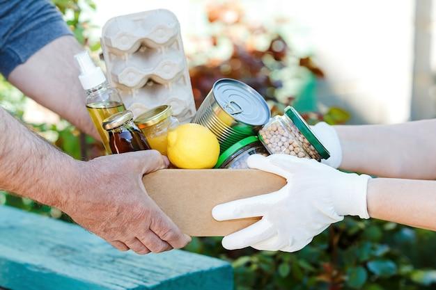 Волонтер передает картонную коробку с кашами, консервами, яйцами, маслом.