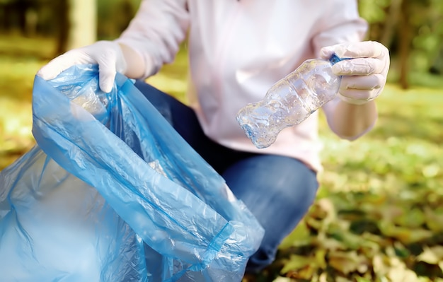 Volunteer picking up the garbage and putting it in biodegradable trash-bag on outdoors.