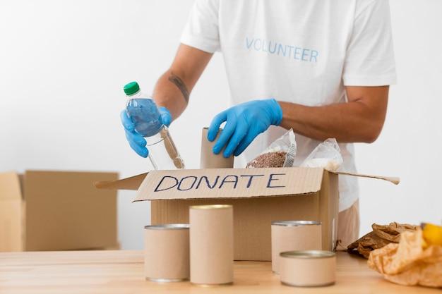 Волонтер кладет разные вкусности в коробки для пожертвований
