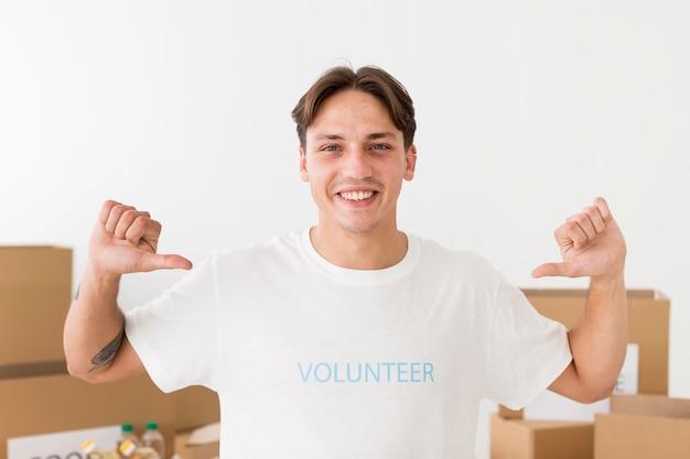 Волонтер указывая на свою футболку