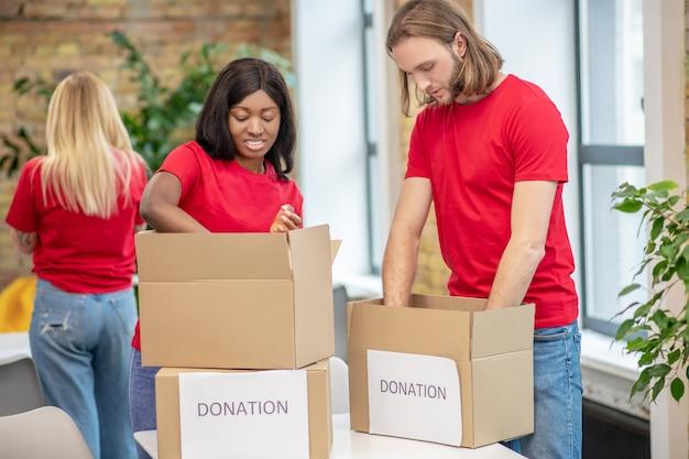 자원 봉사 프로그램. 상자에 기부금을 포장하는 동일한 티셔츠에 젊은 초점을 맞춘 백인 남자와 어두운 피부의 소녀