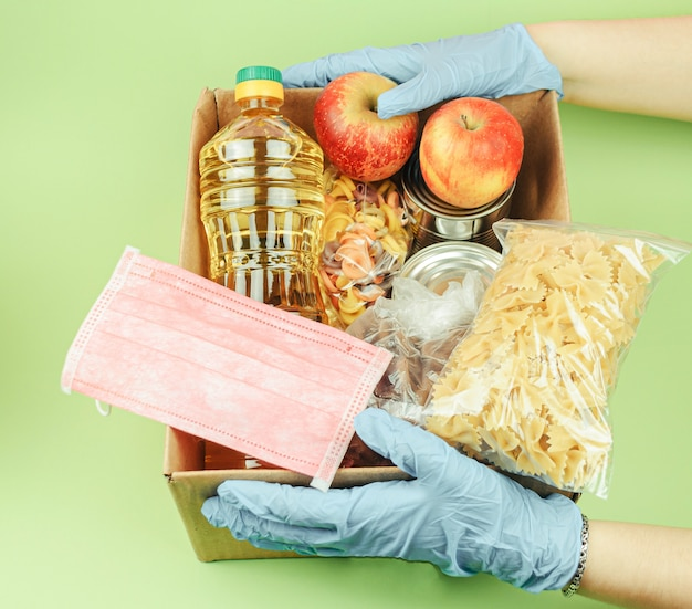 Volunteer in protective gloves with a donation of food boxes on a green background.