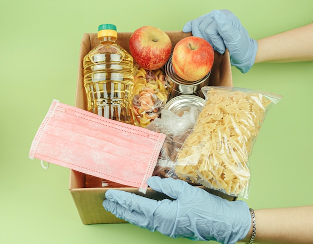 Volunteer in protective gloves with a donation of food boxes on green