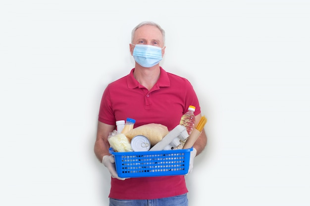 Volunteer in protective mask and gloves delivery donation box at home.