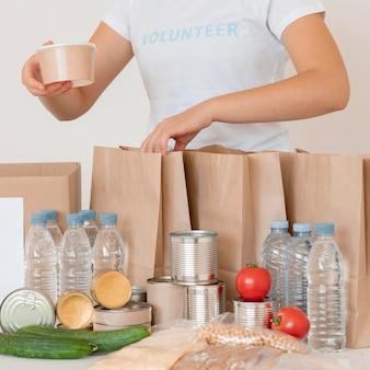 Volontari mettendo cibo cotto e acqua per la donazione in borsa