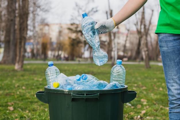 Волонтер кладет пластиковые бутылки в корзину