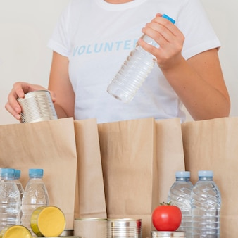Волонтер кладет бутылку с водой в сумку для пожертвования