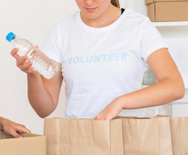 寄付用の水をバッグに入れるボランティア