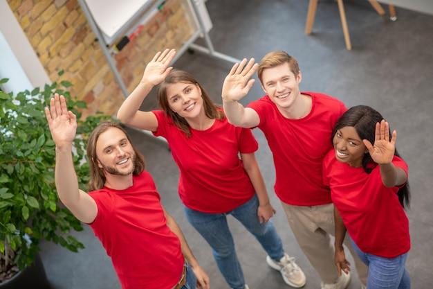 자원 봉사 팀. 낮에 손을 흔들며 자선 단체 건물에 서있는 젊은 행복 자원 봉사자 팀