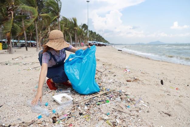 Волонтер-турист убирает мусор и пластиковый мусор на грязном пляже в большую синюю сумку