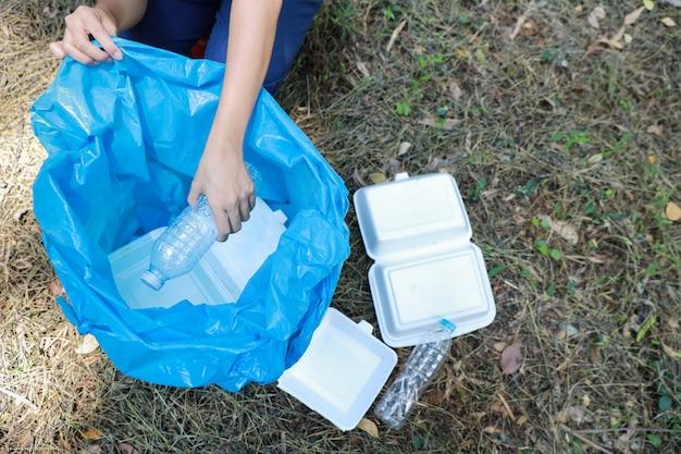 Волонтер-турист убирает мусор и пластиковый мусор в грязном лесу в большую синюю сумку