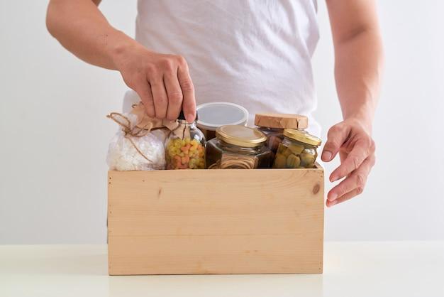 貧しい人々のための食糧の箱を持ったボランティア。寄付のコンセプト。