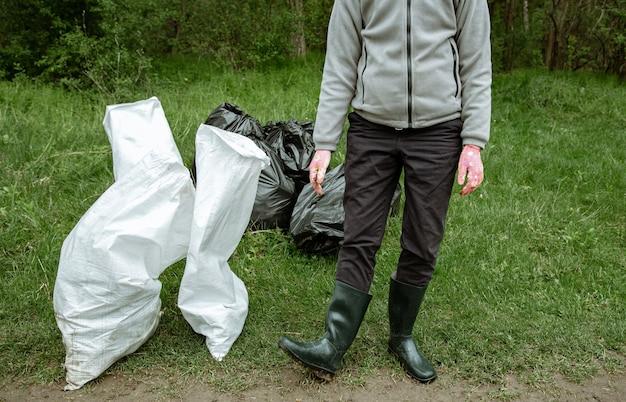 Volontariato con un sacco della spazzatura in un viaggio nella natura, pulendo l'ambiente