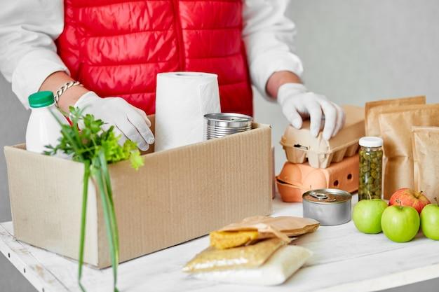 Волонтер с хирургическими перчатками кладет еду в ящик для пожертвований