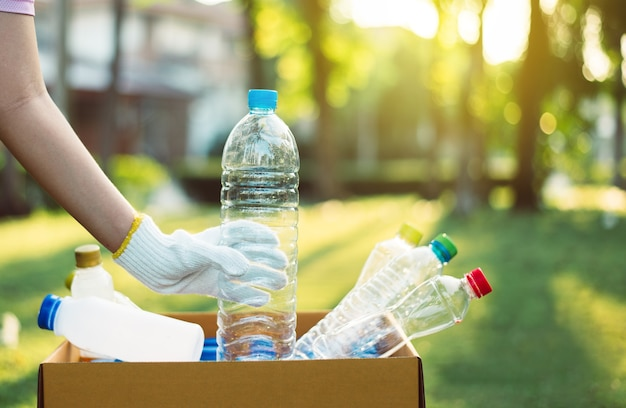 ペットボトルを公共の公園で紙箱に入れているボランティアの女性、リサイクルと廃棄物管理の概念を処分し、良い意識