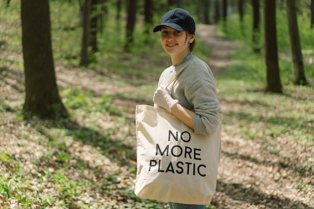 Volunteer woman is cleansed in the forest woman collects plastic