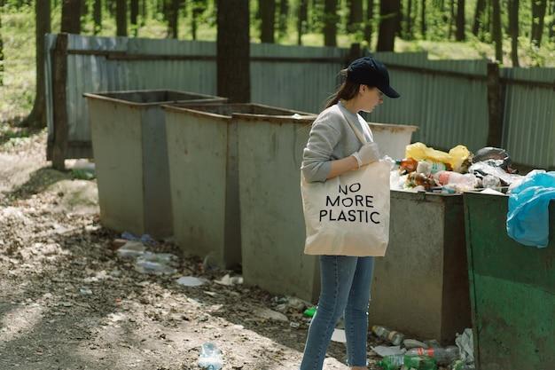 Волонтер убирается в лесу женщина собирает пластик