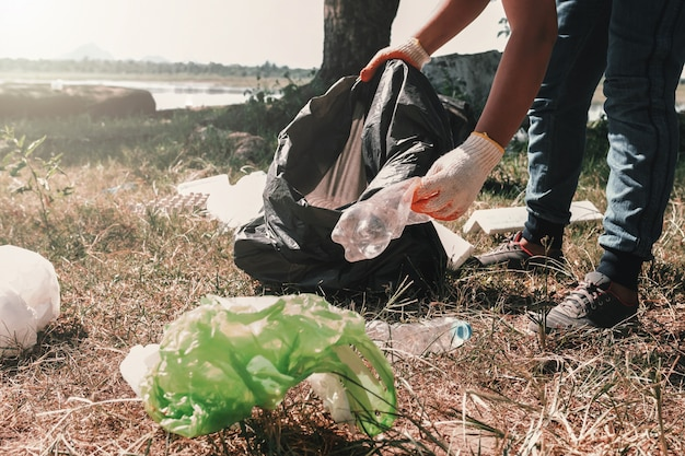 Volunteer woman picking up garbage plastic for cleaning at river park