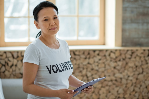 해외 자원 봉사. 카메라를 응시하고 흐린 배경에 포즈를 취하는 동안 클립 보드를 들고 야심 찬 여성 자원 봉사자를 결정했습니다.