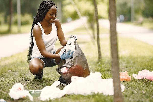 자원봉사와 활동. 친환경적인 아프리카 소녀가 공원을 청소하고 있습니다. 그녀는 가방에 쓰레기를 넣고 있다.