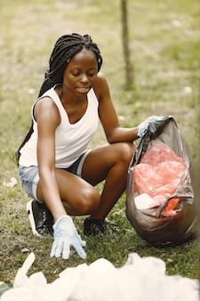 ボランティア活動と行動主義。エコを意識したアフリカの女の子が公園を掃除しています。彼女はゴミを袋に入れています。