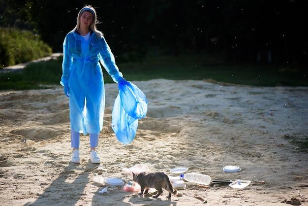Концепция волонтерства, благотворительности, уборки, людей и экологии - волонтер с зоной очистки мусорных пакетов на пляже