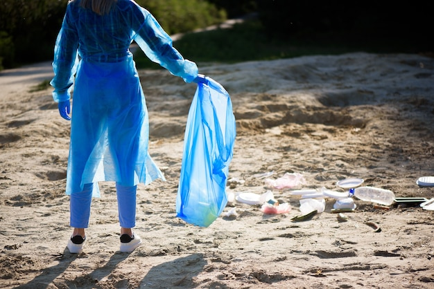 Volunteering, charity, cleaning, people and ecology concept - volunteer with garbage bag cleaning area on the beach