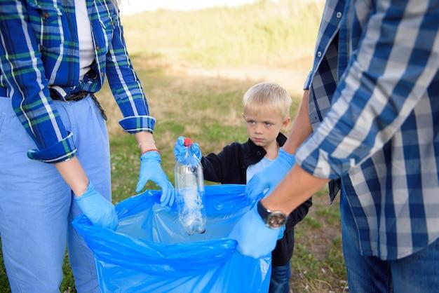 Волонтерство, благотворительность, люди и концепция экологии, волонтеры используют мусорный мешок при сборе мусора.