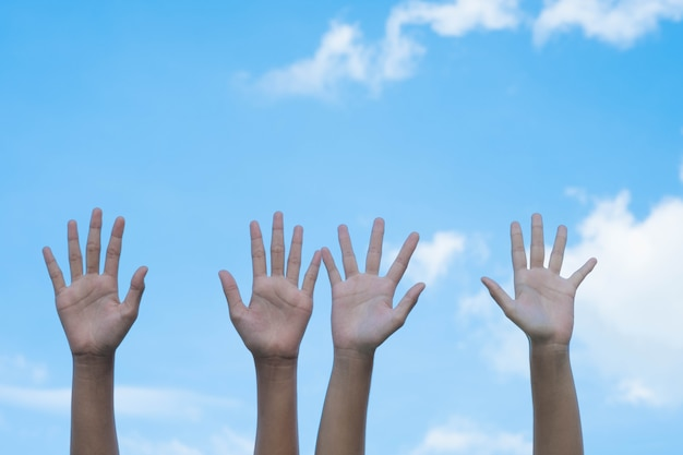 Volunteering concept. hands of people with blue sky on background