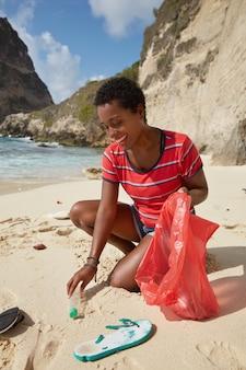 ボランティアのコンセプト。責任ある女性観光客がビーチクリーニングイベントに参加