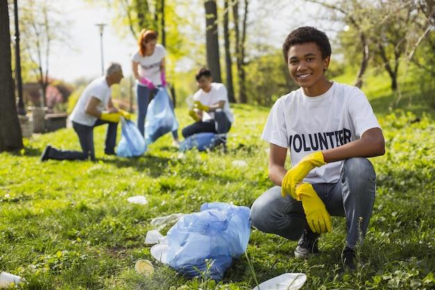 Проблема волонтерства. веселый волонтер мужского пола улыбается в камеру во время сбора мусора