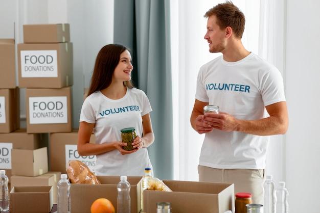 Волонтеры болтают, готовя коробки с едой для благотворительности
