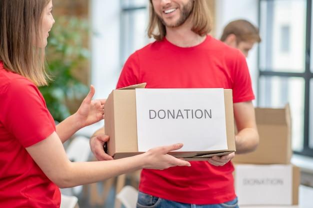 자원 봉사자, 동료. 그의 팔을 뻗어 소녀에게 비문 기부와 함께 포장 상자를 들고 빨간 tshirt에서 웃는 남자