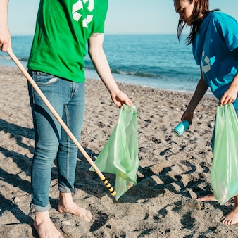 Volunteers collecting waste at the beach with bags
