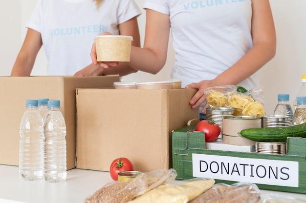 Volontari che riempiono la scatola con cibo per la donazione