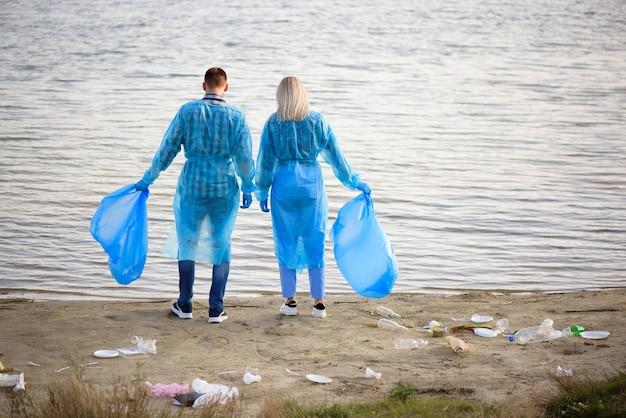 Волонтеры собирают пластиковые бутылки в мешки для мусора, экология, природа, загрязнение, мусор, забота, благотворительное волонтерство, общественная среда.