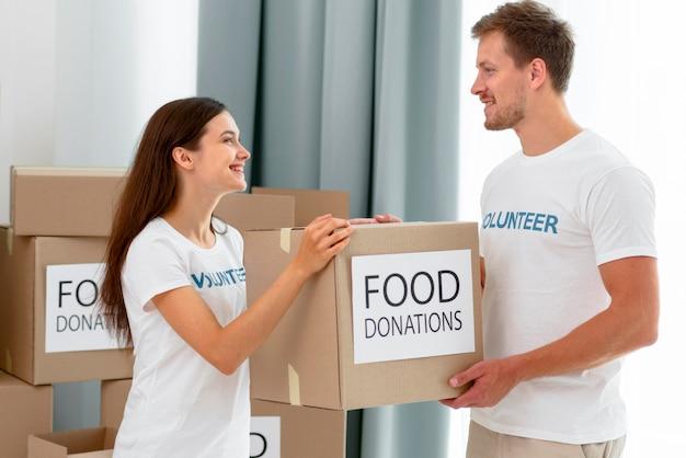Волонтеры обрабатывают коробки с пожертвованиями продуктов питания