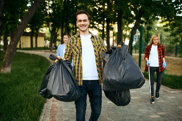 Volunteers holds full plastic trash bags in park, volunteering. male person cleans forest, ecological restoration, eco lifestyle, garbage collection and recycling, ecology care, environment cleaning