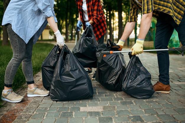 Волонтеры держат пластиковые контейнеры для мусора в парке, волонтерство
