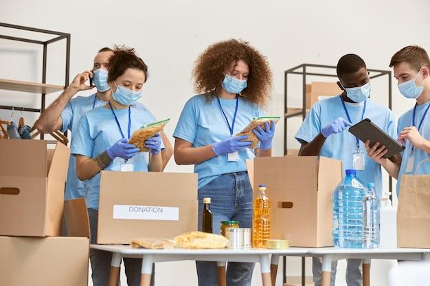 보호 마스크와 장갑을 낀 자원봉사자들이 판지 상자에 음식과 물을 포장하는 것을 분류합니다.